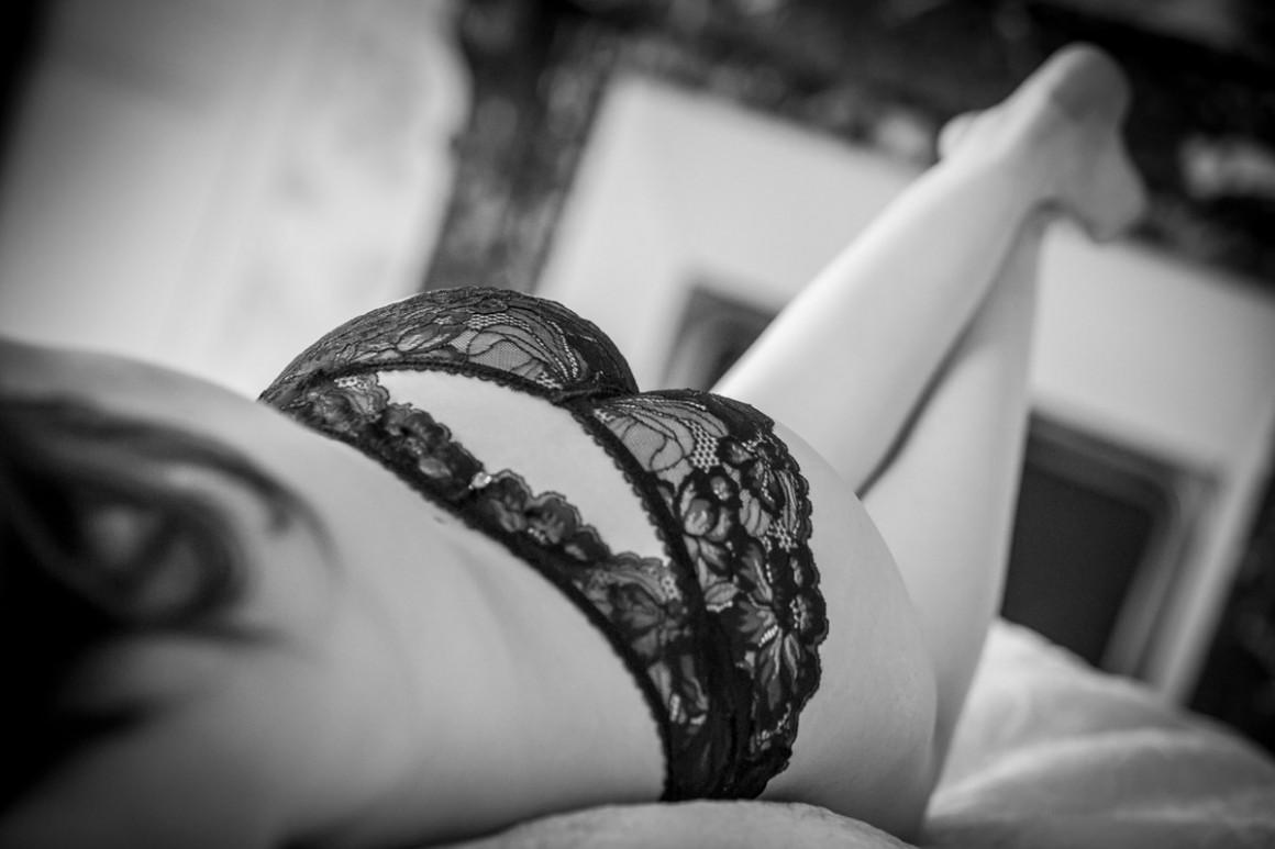 allongée sur un lit en lingerie noire et sexy pour séance book glamour de charme. Boudoir à Bourges